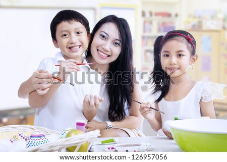 Mother and children are painting in a classroom - stock photo
