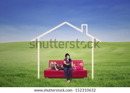 Mother and children enjoying on red sofa with dream house picture outdoor - stock photo