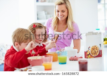 Mother And Children Having Breakfast In Kitchen Together - stock photo