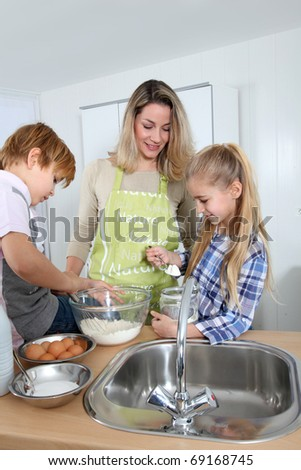 Mother and children in kitchen preparing cake - stock photo