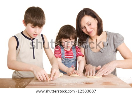 mother and children in the kitchen making a dough