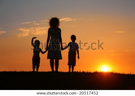 Mother and children on sunset silhouette - stock photo