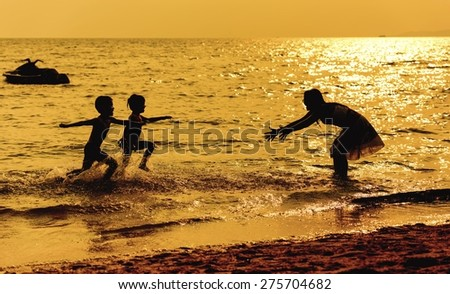 Mother and children playing on the beach - stock photo