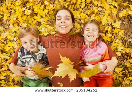 Mother and children playing outdoor with autumn leaves - stock photo