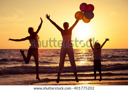 Mother and children playing with balloons on the beach at the sunset time. Concept of friendly family. - stock photo
