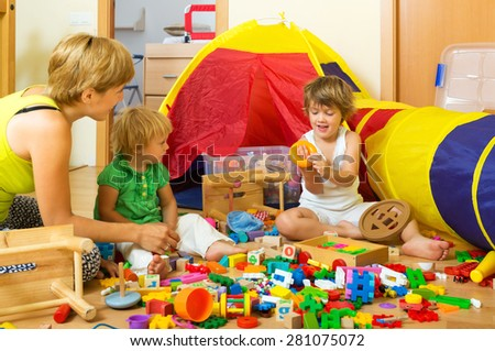 Mother and children playing with  toys in home - stock photo