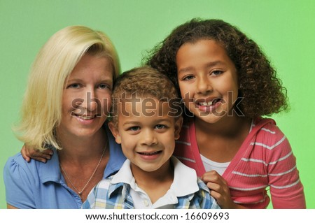 Mother and children's portrait isolated on a green background - stock photo