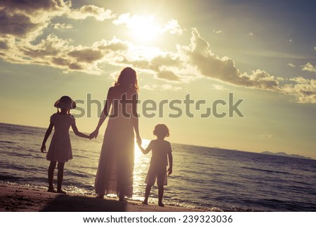 Mother and children standing on the beach at the sunset time. Concept of friendly family. - stock photo