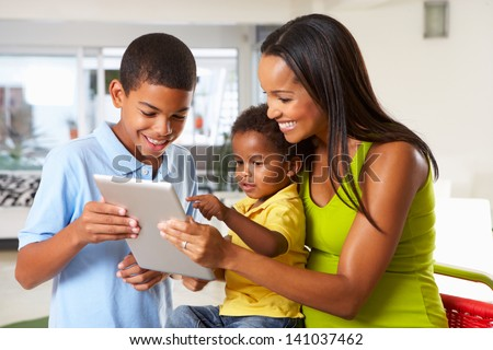 Mother And Children Using Digital Tablet In Kitchen Together