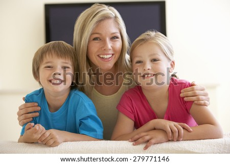 Mother And Children Watching Widescreen TV At Home - stock photo