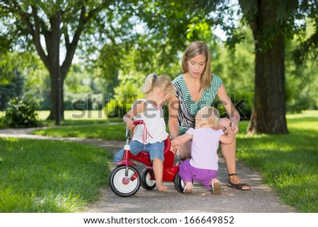 Mother and children with tricycle on walkway in park - stock photo