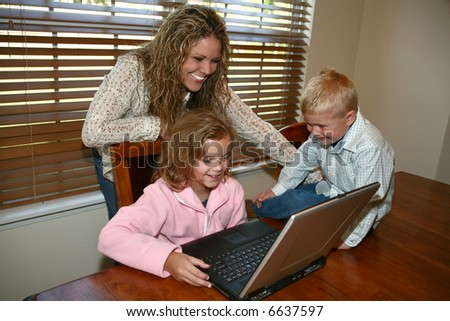 Mother and children working on laptop in kitchen.