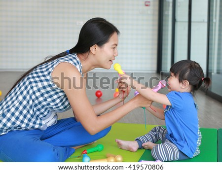 Mother and Cute asian baby girl playing plastic microphone at the Kid room - stock photo