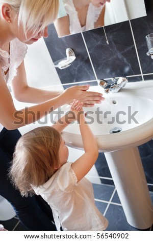 Mother and cute child washing their hands in the bathroom - stock photo