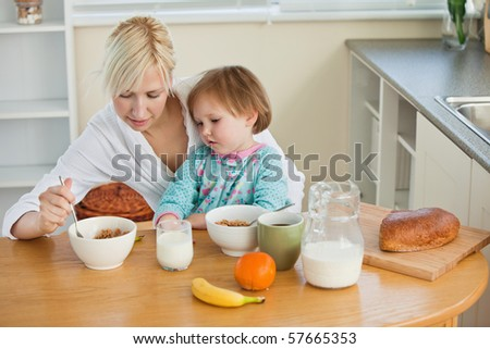 Mother and cute daughter having breakfast in kitchen