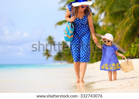 mother and cute little daughter walking on tropical beach - stock photo