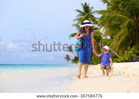 mother and cute little daugther walking on tropical beach - stock photo