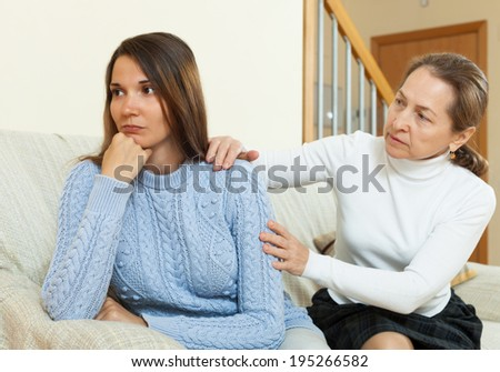Mother and daughter after quarrel on sofa  in home interior - stock photo