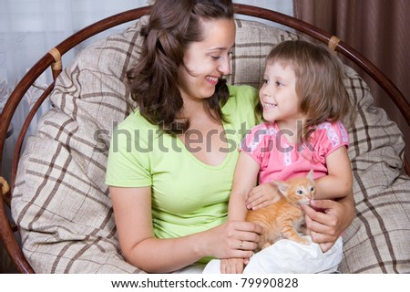 mother and daughter and the kitten,  interior - stock photo