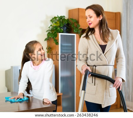 Mother and daughter are cleaning the house. Mom is vacuuming the floor and girl is wiping of dust from the table - stock photo