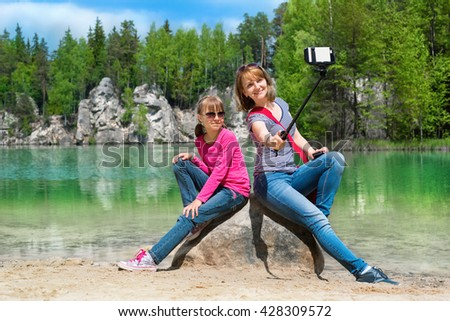 Mother and daughter are doing Selfe on the shore of Piskovna lake. National Park of Adrspach-Teplice rocks. Rock Town. Czech Republic. - stock photo