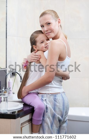 Mother and daughter are in bathroom hugging each other - stock photo