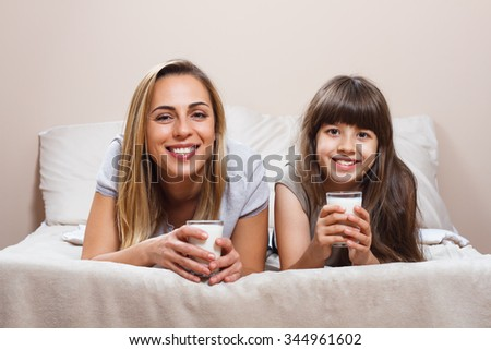 Mother and daughter are lying on bed and drinking milk.Glass of milk for mother and daughter
