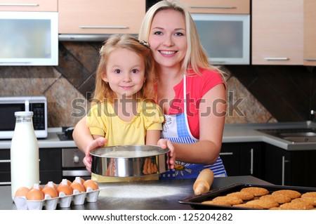 Mother and daughter are preparing baked together in the kitchen - stock photo