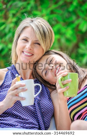 mother and daughter are relaxing at home drinking tea - stock photo