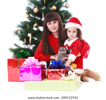 Mother and daughter around the Christmas tree next to the boxes which are gifts-isolated on white background - stock photo