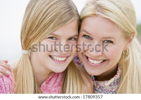 Mother and daughter at beach smiling - stock photo