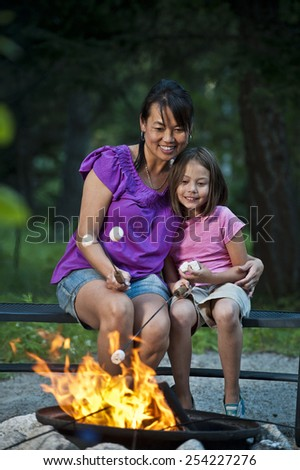 Mother and Daughter at Campfire - stock photo
