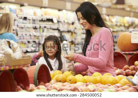 Mother And Daughter At Fruit Counter In Supermarket