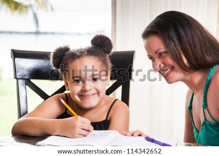 Mother and daughter at home. Mom teachs little girl homework. - stock photo
