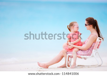Mother and daughter at tropical beach relaxing on chair