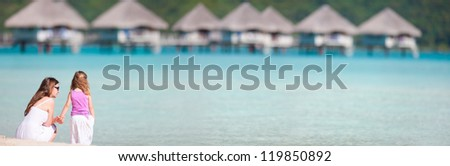 Mother and daughter at tropical resort beach - stock photo