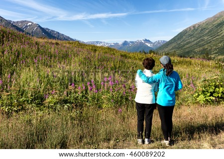 Mother and daughter, backs to camera, looking at wild flowers in field with mountains and sky in background. Selective focus on people.  - stock photo