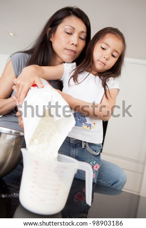 Mother and daughter baking together, measuring out dry ingredient - stock photo
