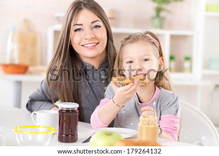 Mother and daughter breakfast in the kitchen. Cute little girl eats bread with peanut butter. Looking at Camera. - stock photo