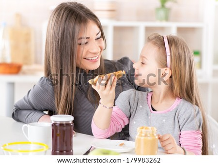 Mother and daughter breakfast in the kitchen. Cute little girl eats bread with peanut butter.
