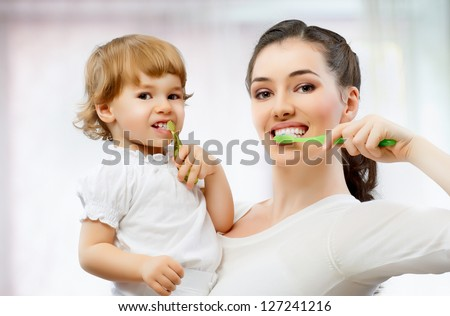 mother and daughter brush their teeth - stock photo
