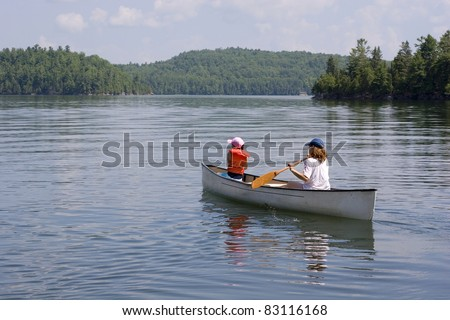 Mother and daughter canoeing on a lake - stock photo