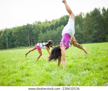 Mother and daughter cartwheeling in meadow - stock photo