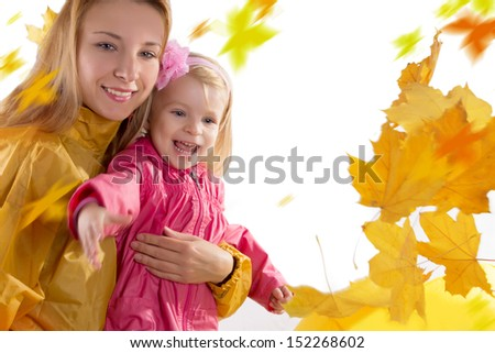 Mother and daughter catching falling leaves, over white