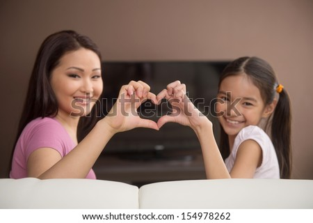 Mother and daughter. Cheerful mother and daughter gesturing and smiling while sitting in front of the TV - stock photo