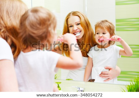 mother and daughter child girl brushing her teeth toothbrushes front of the mirror in the bathroom - stock photo