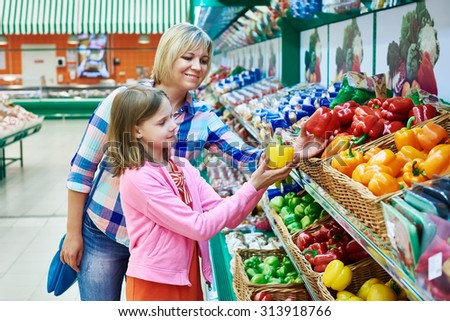 Mother and daughter chooses bell peppers in the supermarket - stock photo