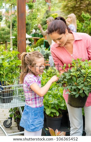 Mother and daughter choosing flowers at garden centre shop