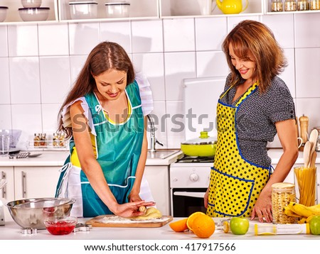 Mother and daughter cooking food at kitchen. Cooking at home. - stock photo