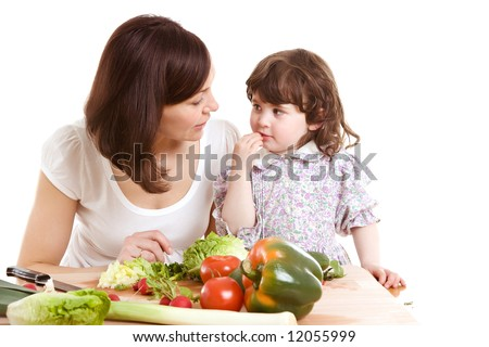 mother and daughter cooking salad at the kitchen - stock photo